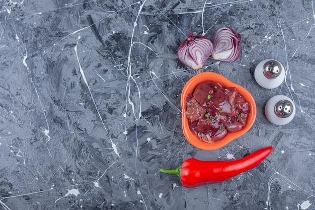 파란색 표면에 양파, 소금, 후추 옆에 닭고기 간 한 그릇