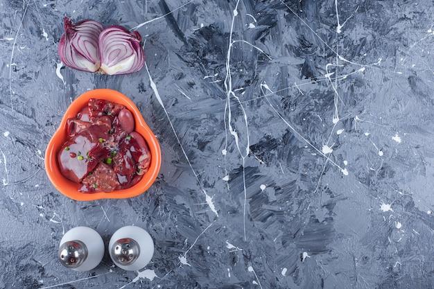青いテーブルの上のタマネギ、塩、コショウの横にある鶏レバーのボウル。