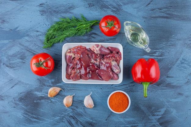 파란색 표면에 딜, 기름, 마늘 옆에있는 닭 내장 한 그릇.