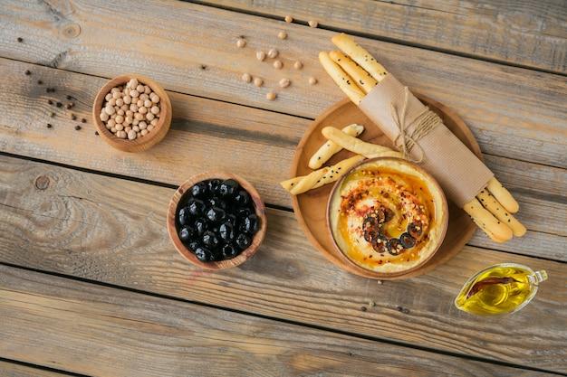 Чаша домашнего хумуса из нута с оливковым маслом, маслинами и хрустящими хлебцами.