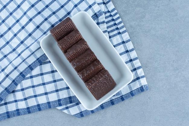 Чаша с шоколадной глазурью на хрустящей вафельной плитке на полотенце, на мраморном столе.