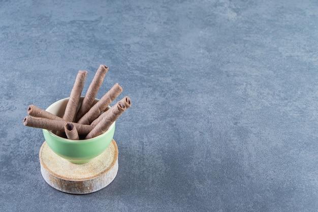 초콜릿 웨이퍼 한 그릇은 대리석 배경에 있는 판자 위에 있습니다.