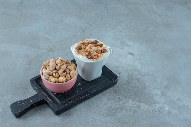 Миска кукурузных хлопьев и чашка капучино на доске, на синем фоне. фото высокого качества