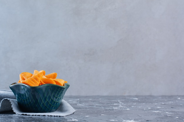 대리석 표면에 있는 천 조각에 있는 바삭한 감자 칩 한 그릇