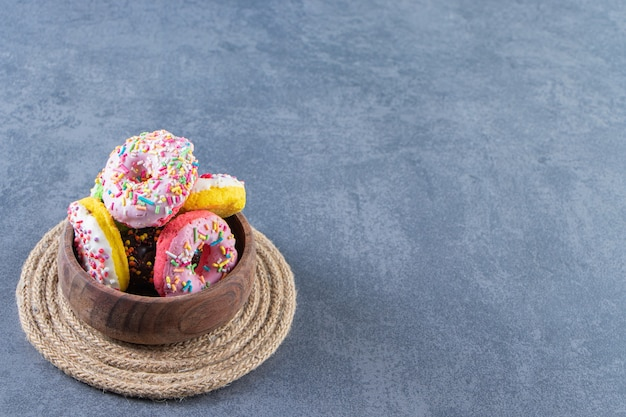 Миска с пончиками на подставке на мраморной поверхности