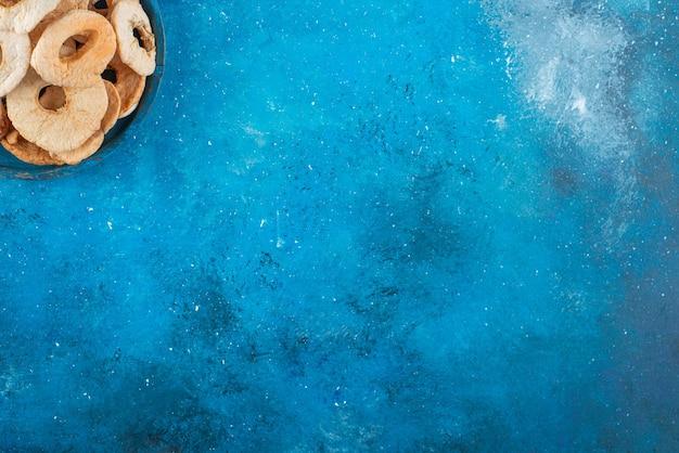 青いテーブルの上に、乾燥したリンゴのリングのボウル。
