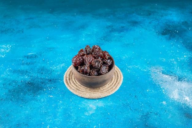 青いテーブルの上に、トリベットの上にプルーンのボウル。