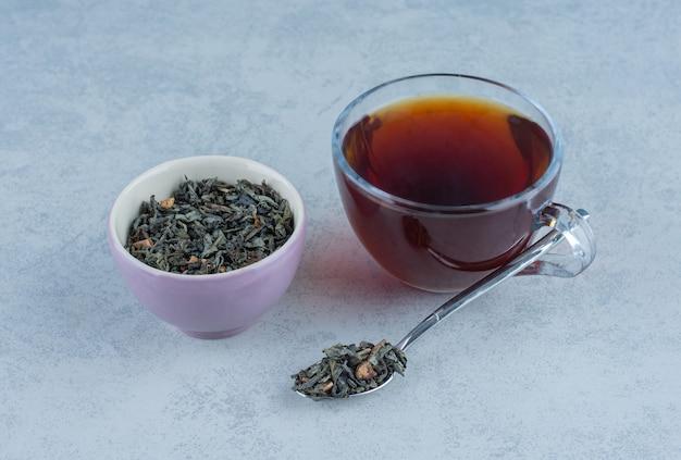 乾燥した茶葉のボウルと大理石のスプーンでお茶のカップ。