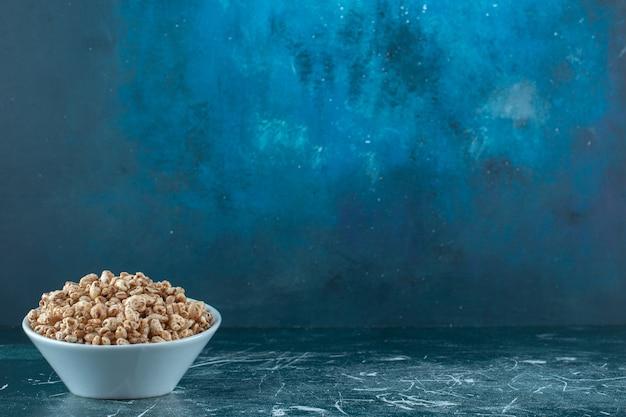 青い背景に、乾燥したコーンフレークのボウル。高品質の写真