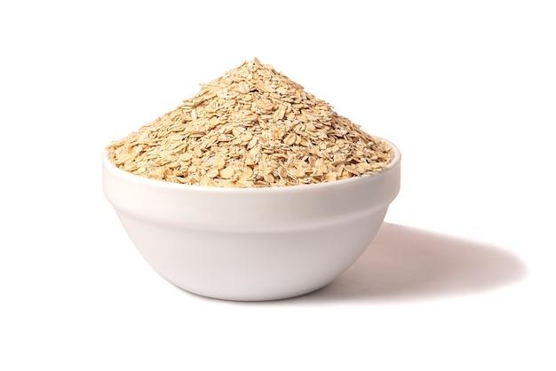 ドライオートミールのボウル。ヘルシーでシンプルな朝食用食品。ダイエットのコンセプト。白い背景に。