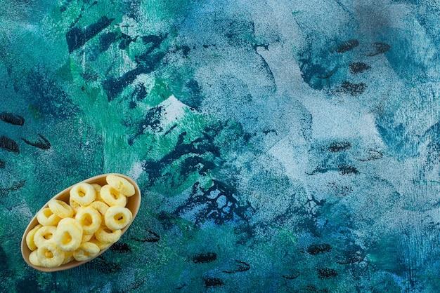 青いテーブルの上に、風味豊かなコーンリングのボウル。