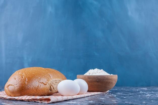 Чаша с мукой, лавашем и нарезанным хлебом на кухонном полотенце на синем столе.
