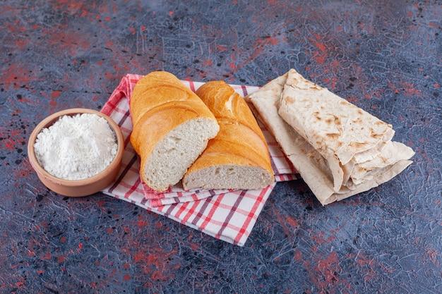 Миска с мукой, лавашем и нарезанным хлебом на кухонном полотенце, на синем.