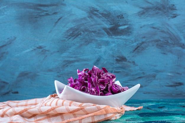 Миска свежей красной капусты на кухонном полотенце