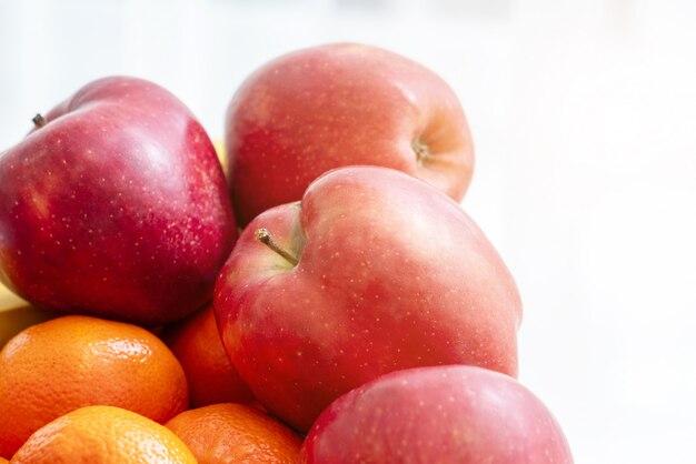 白い壁にフルーツのボウル。リンゴとオレンジ