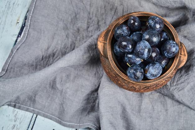 灰色のテーブルクロスに庭の梅のボウル。