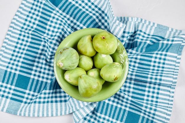 白地に青いテーブルクロスが付いた緑のイチジクのボウル。