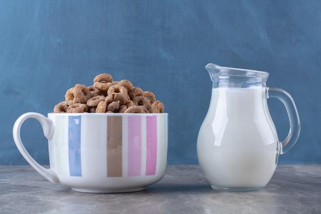 우유의 유리 항아리와 함께 건강 한 초콜릿 시리얼 반지의 그릇.