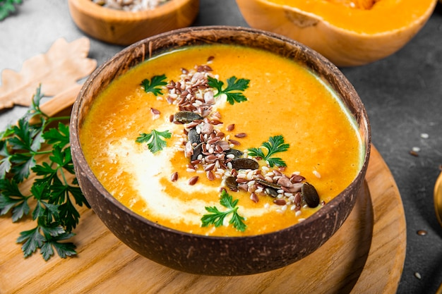 自家製カボチャスープのボウルゴマと亜麻の種子のクローズアップ暖かい秋の食べ物
