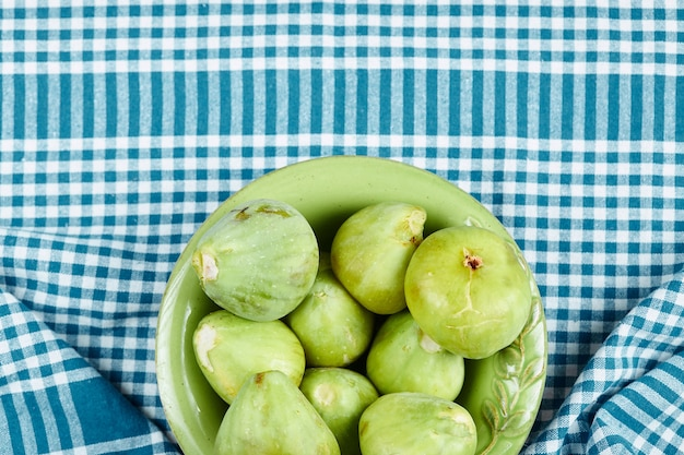 青いテーブルクロスにジューシーな緑のイチジクのボウル。