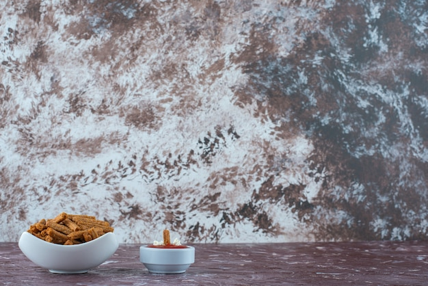 대리석 테이블에 있는 그릇에 케첩과 바삭한 빵 부스러기 한 그릇.