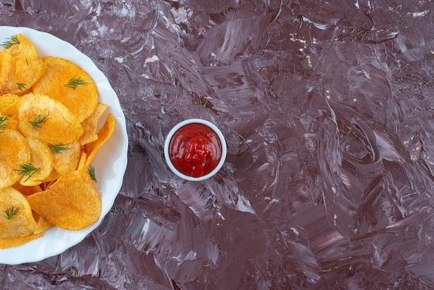 대리석 테이블에 접시에 케첩과 감자 튀김 한 그릇.