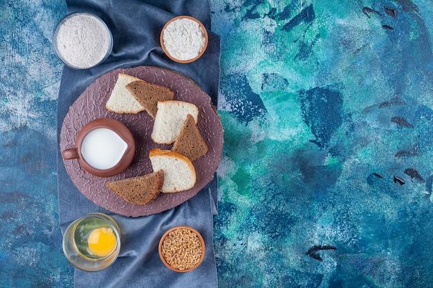 青いテーブルの上の穀物と小麦粉の隣のボード上のミルクとスライスされたパンのボウル。