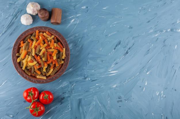 Миска разноцветных сырых спиральных макарон со свежими красными помидорами и чесноком.