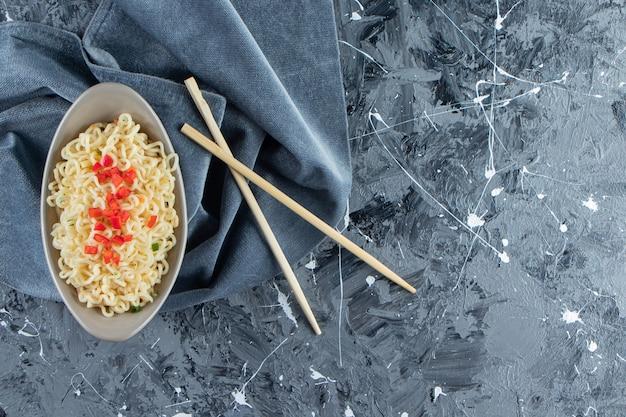 Миска с лапшой рядом с палочками для еды на кусках ткани на мраморном фоне.
