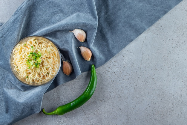 대리석 배경에 천 조각에 국수, 후추, 마늘 한 그릇.