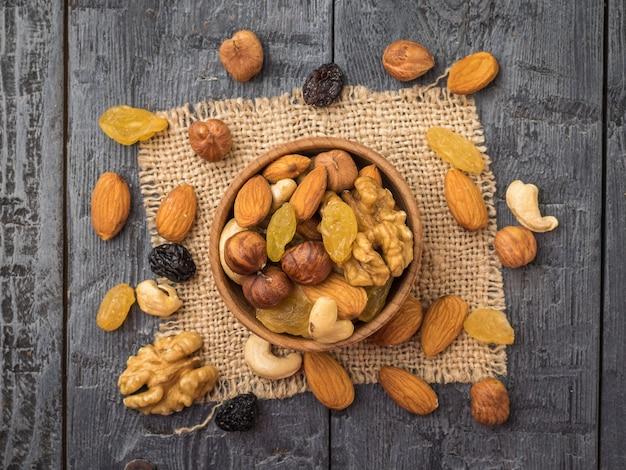 Миска ореховой смеси на куске мешковины на деревянном столе. натуральная здоровая вегетарианская пища. плоская планировка.