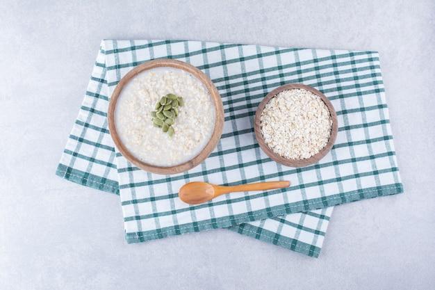 Миска овса и миска овсянки с пепитасом рядом с ложкой на полотенце на мраморной поверхности.
