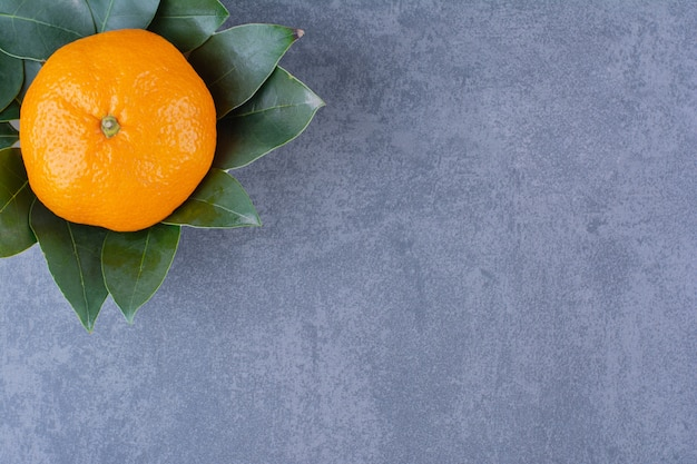 Миска с апельсинами и листьями на мраморном столе.