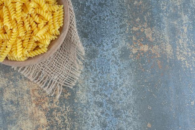 Миска с макаронами на полотенце на мраморной поверхности.