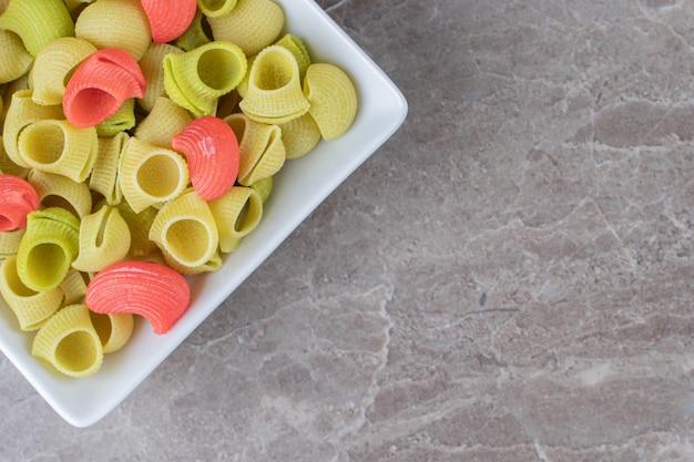 Чаша с макаронами, готовыми к приготовлению, на мраморной поверхности.