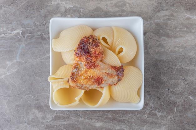 Тарелка макарон с болоньезе на мраморе.