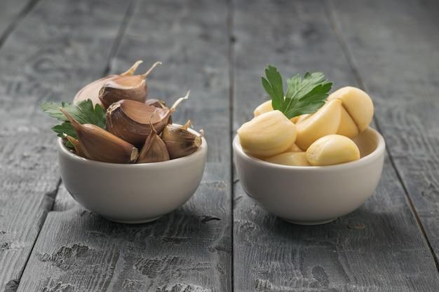 木製のテーブルの上に皮をむいたニンニクのボウルと皮をむいていないニンニクのボウル。キッチンに人気のスパイス。