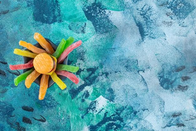 파란색 테이블에 마멀레이드 스틱이 달린 플라스틱 햄버거 한 그릇.
