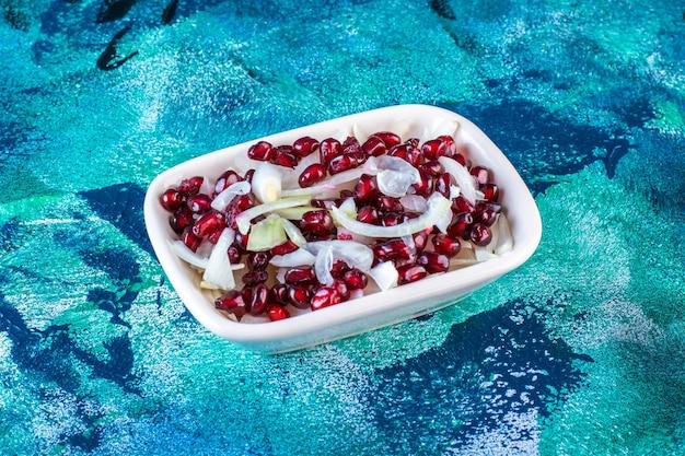 얇게 썬 양파를 곁들인 석류 가자미 한 그릇