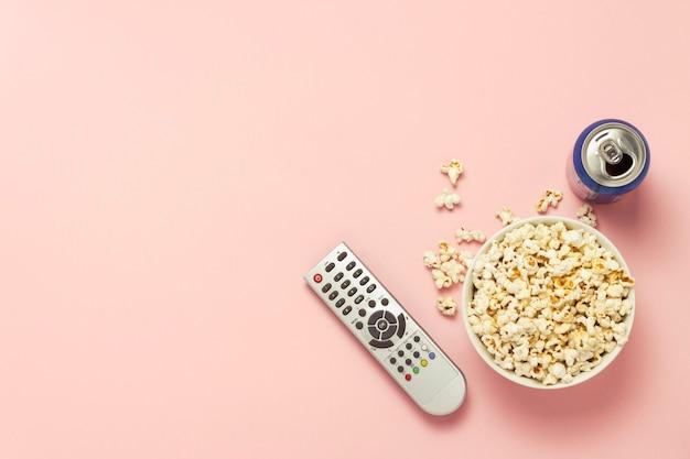 Чаша с попкорном, пульт от телевизора, банка с напитками на розовом фоне. концепция просмотра тв, кино, сериалов, спортивных передач, шоу. плоская планировка, вид сверху.