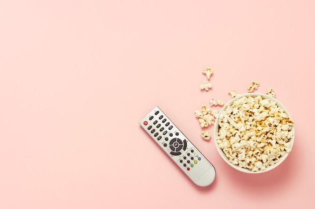 Чаша из попкорна и тв пульт на розовом фоне. концепция просмотра тв, кино, сериалов, спортивных передач, шоу. плоская планировка, вид сверху.