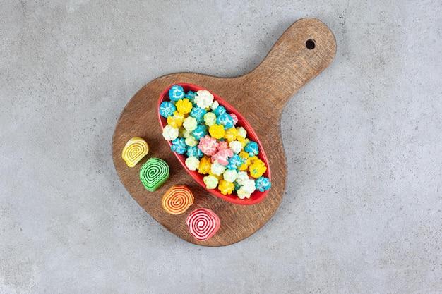 Миска конфет попкорна рядом с мармеладом на деревянной доске на мраморной поверхности