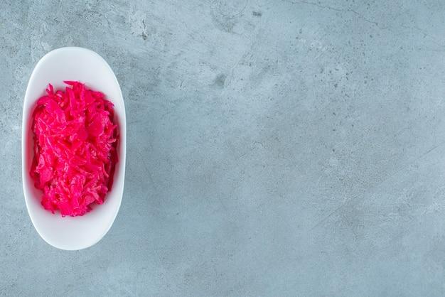 Чаша с красной квашеной квашеной капустой на синем столе.