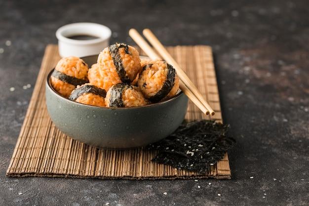 참깨와 김을 곁들인 주먹밥 한 그릇, 어두운 배경에 간장, 젓가락과 함께 제공됩니다. 복사 공간이있는 측면보기. 수평 방향