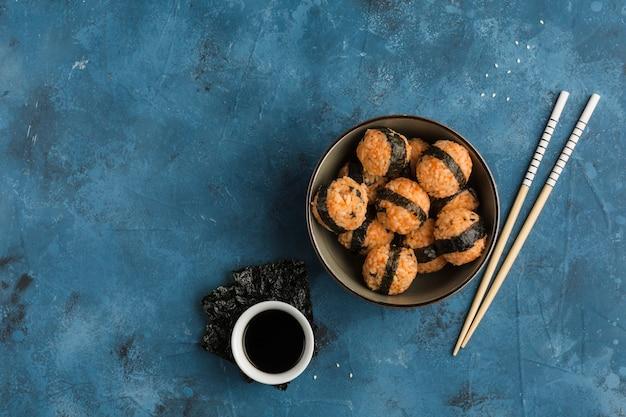 참깨와 김을 곁들인 주먹밥 한 그릇에 진한 파란색 배경에 간장과 젓가락을 곁들였습니다. 복사 공간이있는 측면보기. 수평 방향
