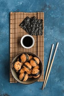 참깨와 김을 곁들인 주먹밥 한 그릇에 진한 파란색 배경에 간장과 젓가락을 곁들였습니다. 복사 공간이있는 측면보기. 수직 방향