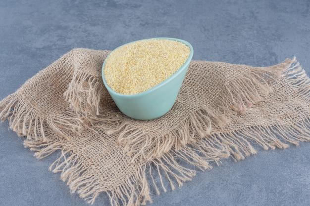 Миска с рисом на полотенце на мраморном фоне.