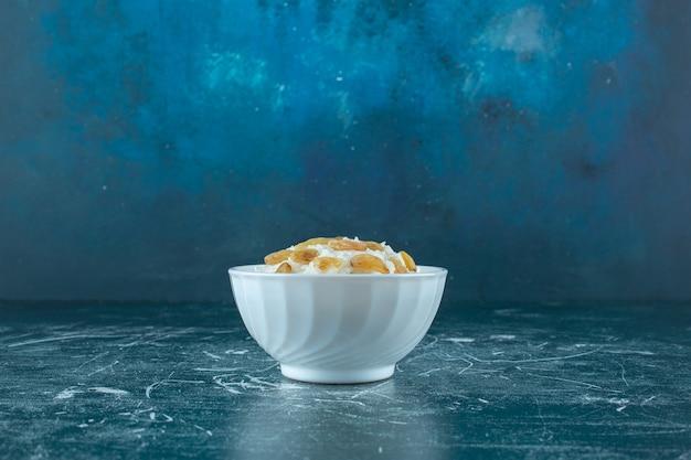Чаша рисового пудинга с изюмом, на синем фоне. фото высокого качества