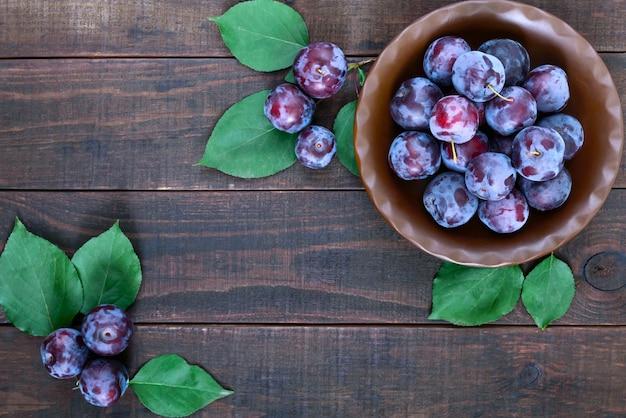 Чаша спелых голубых слив алычи на темном деревянном столе