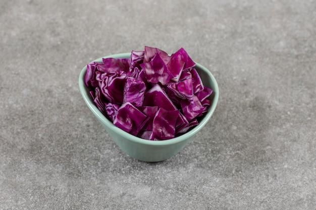 돌 테이블에 얇게 썬된 보라색 양배추의 그릇.